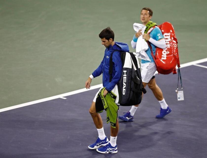 El tenista serbio Novak Djokovic (i) y el alemán Philipp Kohlschreiber (d) abandonan la pista a causa de la lluvia durante un partido del torneo de Indian Wells disputado este lunes en Indian Wells, California (EE.UU.). EFE