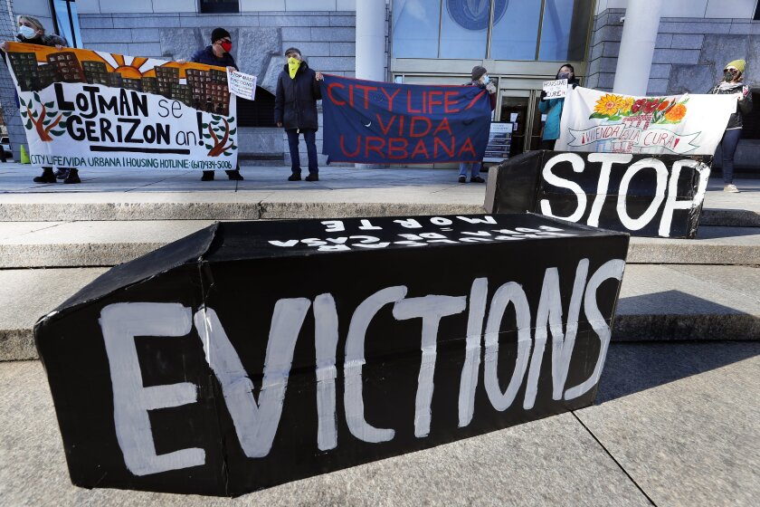 """People outside a courthouse display signs, including the message """"Stop Evictions"""""""