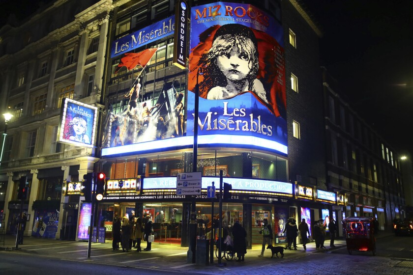 """People leave the Sondheim Theatre, in London, where """"Les Miserables"""" returned to the stage for the first time in almost nine months at the start of December, and now closes as London moves into the highest tier of coronavirus restrictions at midnight as a result of soaring case rates, Tuesday Dec. 15, 2020. (Aaron Chown/PA via AP)"""