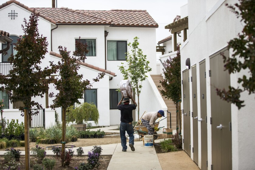 Workers put the finishing touches on the Vernon Village Park Apartments. The 45-unit complex will double the population of the five-square mile city, located five miles south of downtown Los Angeles.