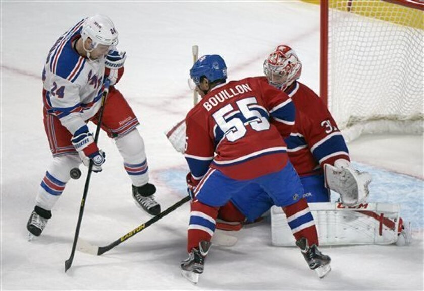 Montreal Canadiens goaltender Carey Price, right, makes a save against New York Rangers' Ryan Callahan (24) as Canadiens' Francis Bouillon defends during first-period NHL hockey game action in Montreal, Saturday, March 30, 2013. (AP Photo/The Canadian Press, Graham Hughes)