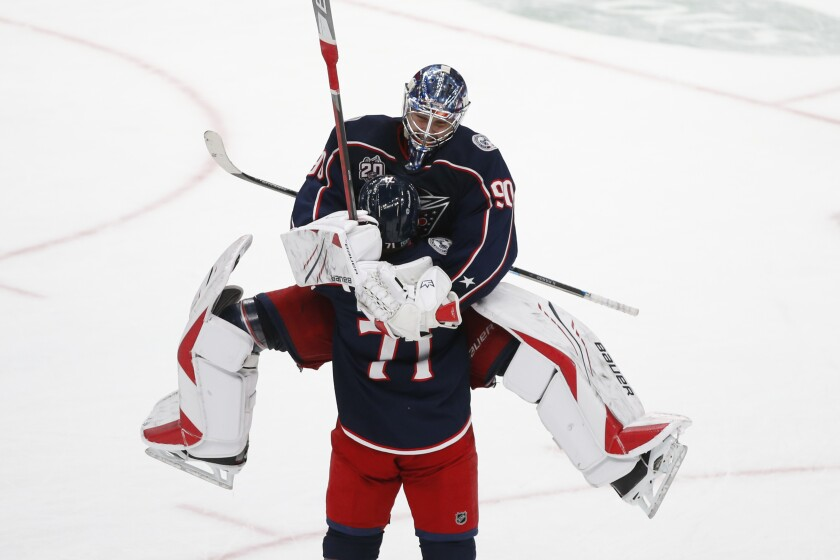 Columbus Blue Jackets' Elvis Merzlikins, top, of Latvia, celebrates their win over the Tampa Bay Lightning with teammate Nick Foligno after an NHL hockey game Saturday, Jan. 23, 2021, in Columbus, Ohio. The Blue Jackets beat the Lightning 5-2. (AP Photo/Jay LaPrete)
