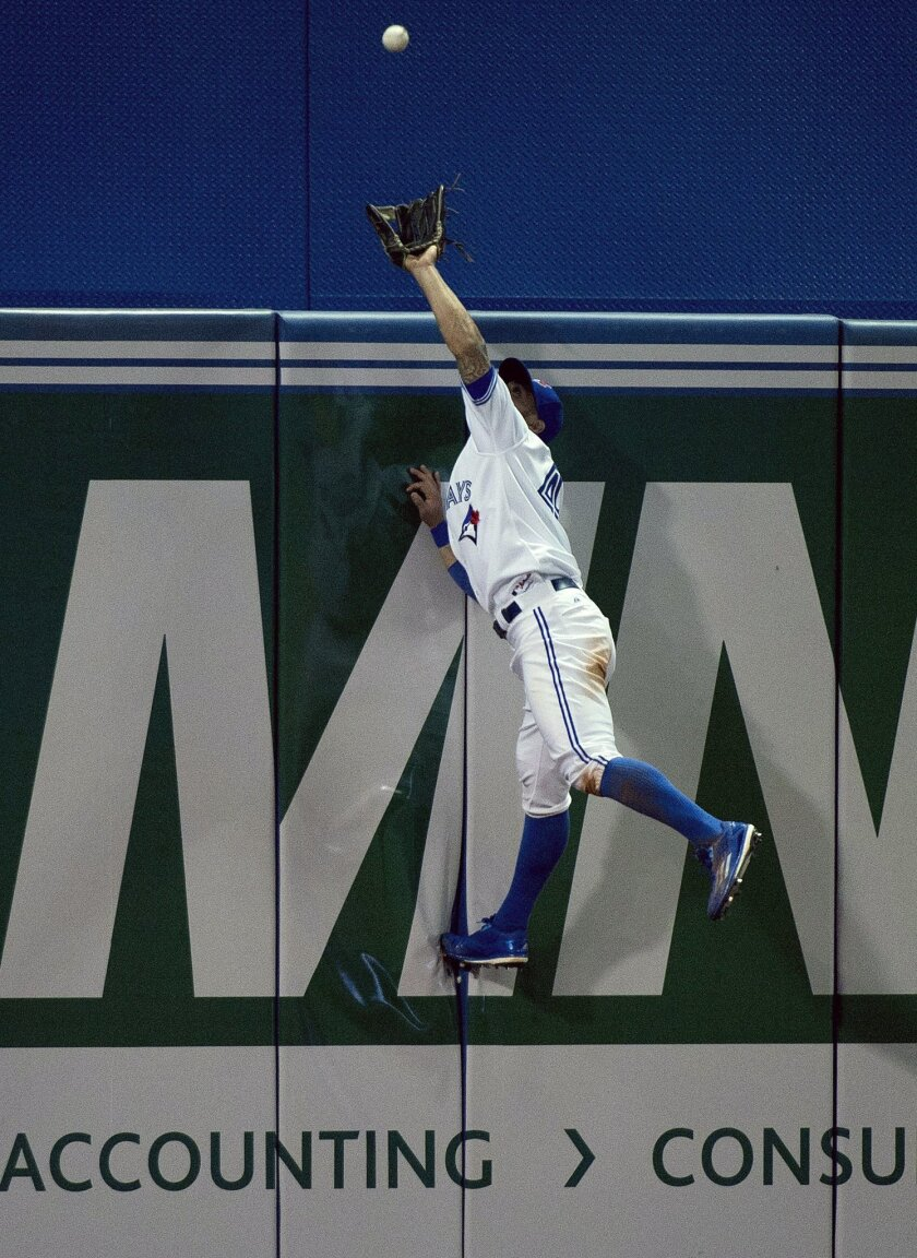 Toronto Blue Jays left fielder Kevin Pillar makes a catch on the other side of the wall hit by Tampa Bay Rays Tim Beckham during the seventh inning of a baseball game, Wednesday, April 15, 2015 in Toronto. (Nathan Denette/The Canadian Press via AP)  MANDATORY CREDIT