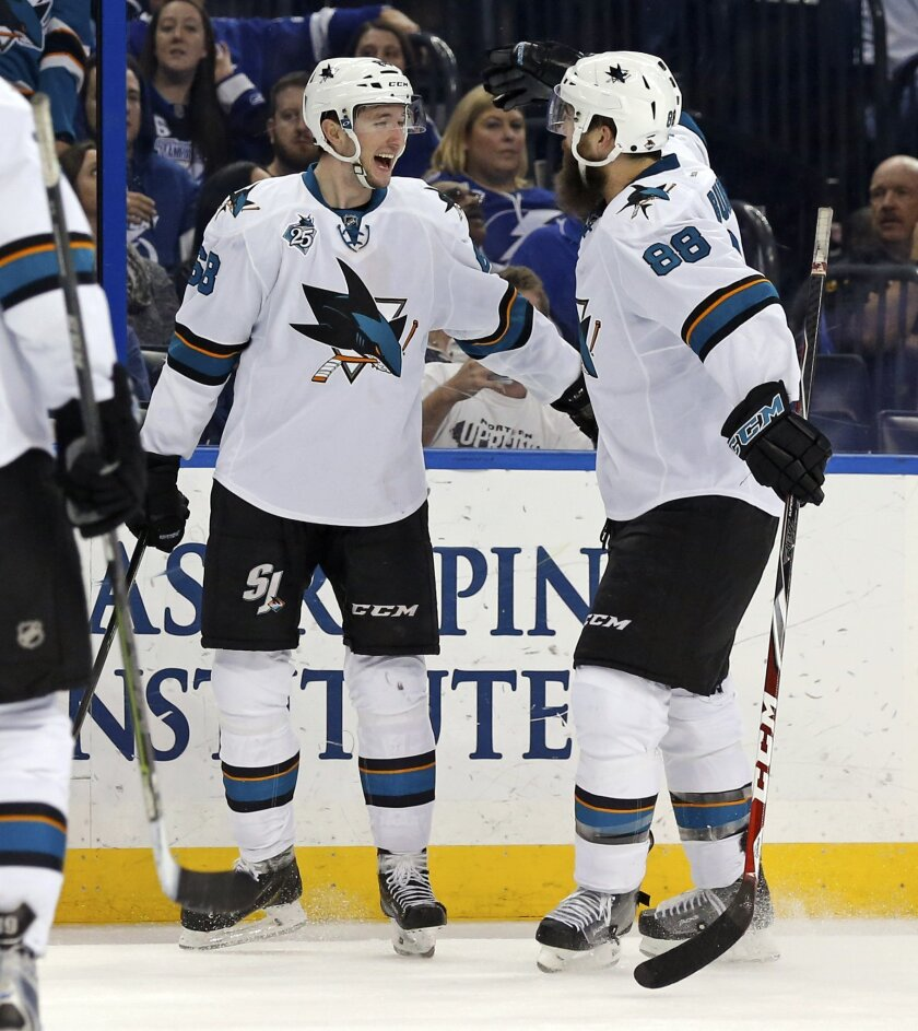 San Jose Sharks' Melker Karlsson, left, of Sweden, celebrates his goal with teammate Brent Burns during the third period of an NHL hockey game against the Tampa Bay Lightning Tuesday, Feb. 16, 2016, in Tampa, Fla. The Sharks won 4-2. (AP Photo/Mike Carlson)