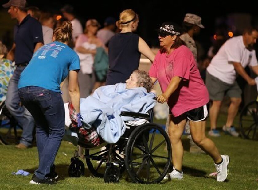 An elderly person is assisted at a staging area at a local school stadium  following an explosion at a fertilizer plant Wednesday, April 17, 2013, in West, Texas. An explosion at a fertilizer plant near Waco caused numerous injuries and sent flames shooting high into the night sky on Wednesday. (AP