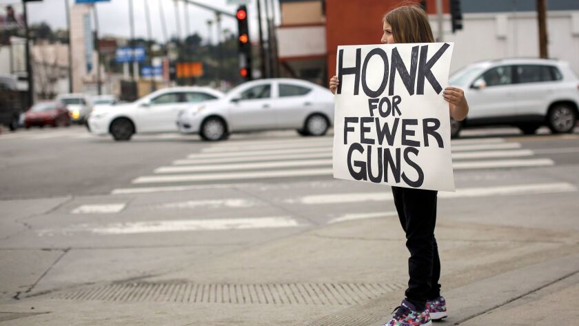 Daisy Simard, 9, holds a sign in protest in Studio City on Sunday. The student-activist group No Guns L.A. held a rally to call for stricter gun control laws.