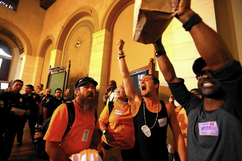 Members of the Los Angeles Community Action Network, a homeless advocate group, protest at City Council meeting where a crackdown on homeless encampments was approved.