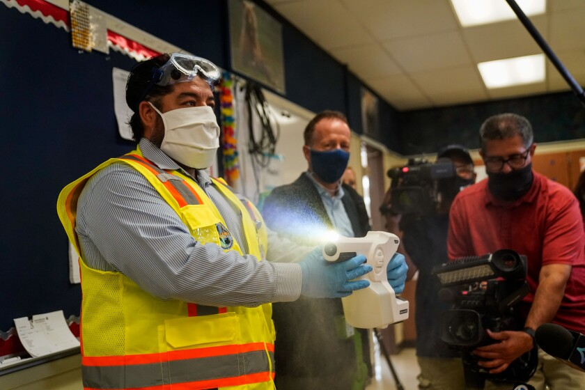 Los Angeles Unified School District staff member Adrian Pacheco demonstrates the use of sanitizing tools.