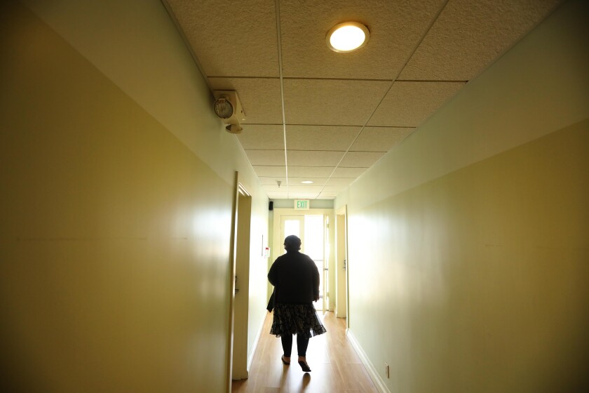 Wendy Brown, 58, walks through the hallway where she now resides at the Cadillac Hotel in Venice.