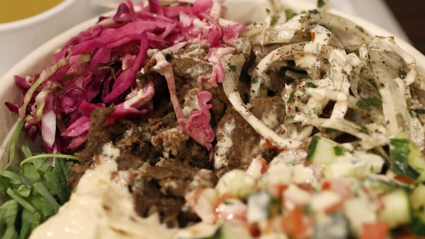 Steak shawarma rice bowl with mixed greens at SAJJ Mediterranean restaurant in Irvine.