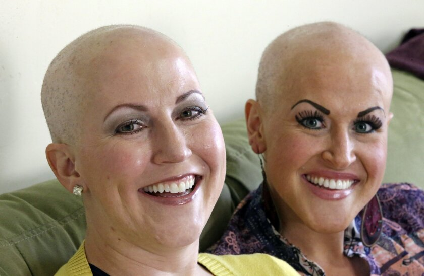 In this Thursday, May 26, 2016, photo, Annette Page, left, and her sister Sharee Page, pose for a photograph at Sharee's home during an interview, in Farmington, Utah. The two Utah sisters have received a breast cancer diagnosis within about two weeks of one another, a coincidence that doctors say