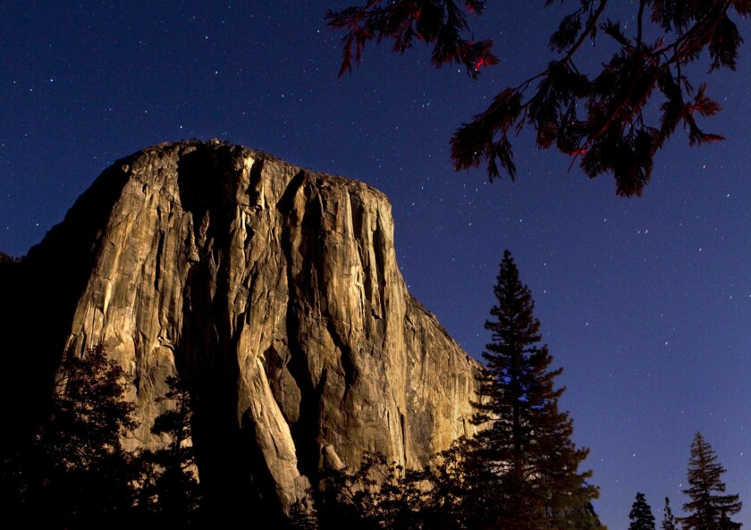 The granite monolith El Capitan is bathed in moonlight in the Yosemite Valley.