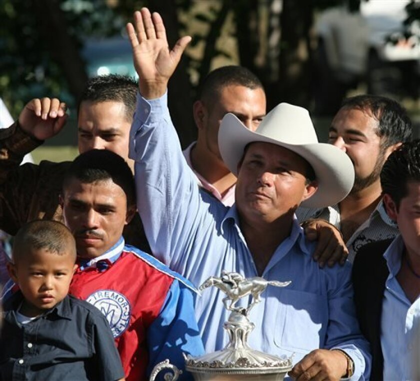 FILE - In this Sept. 6, 2010 file photo, owner Jose Trevino Morales, center, acknowledges the crowd as he stood with the trophy after Mr. Piloto won the All American Futurity horse race at Ruidoso Downs, N.M. Prosecutors told a federal jury on Wednesday, May 8, 2013 that Morales, the man they say is the brother of leaders of Mexico's most blood-soaked criminal organization, used the proceeds from their brothers' ill-gotten gains to bankroll his horse-racing stable. (AP Photo/The El Paso Times, R