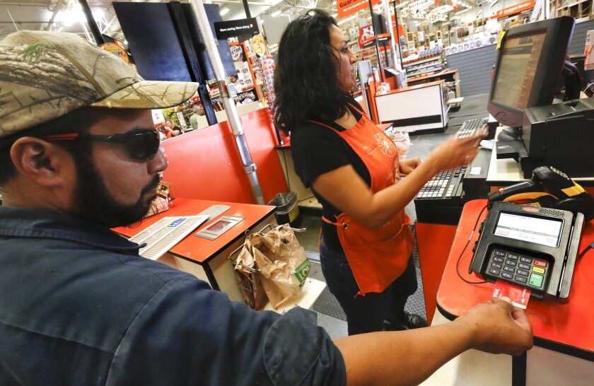 A cashier waits as a customer inserts a credit card into a reader at Home Depot in Burbank.