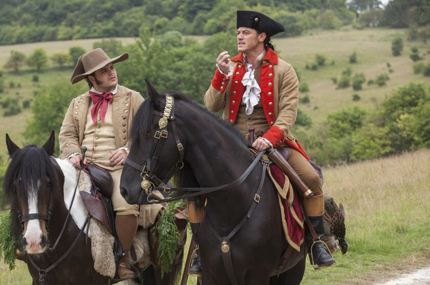 Two men in period costumes on horseback