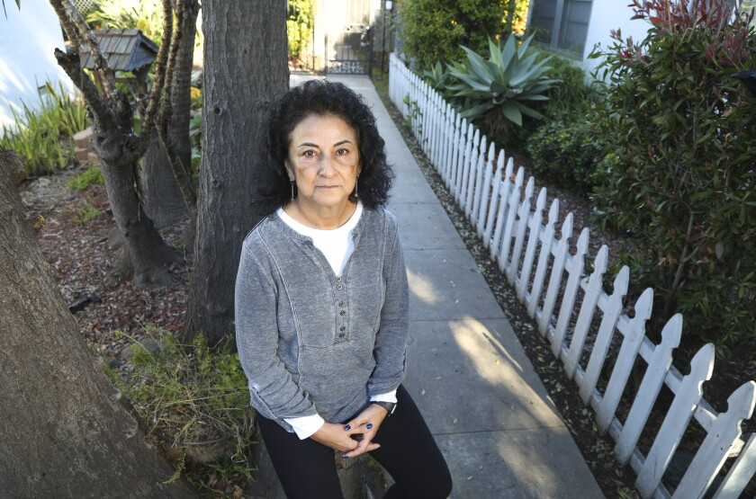 Yolanda Medina poses for photos outside her home on March 27, 2020, in San Diego. Medina says she will continue to pay monthly dues to two gyms because she wants to support the staff.