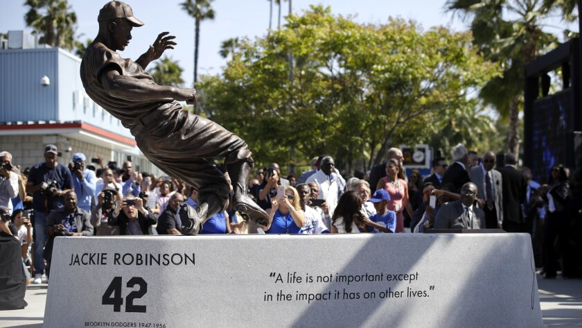 A bronze statue of Dodgers legend Jackie Robinson is unveiled outside Dodger Stadium on Saturday.