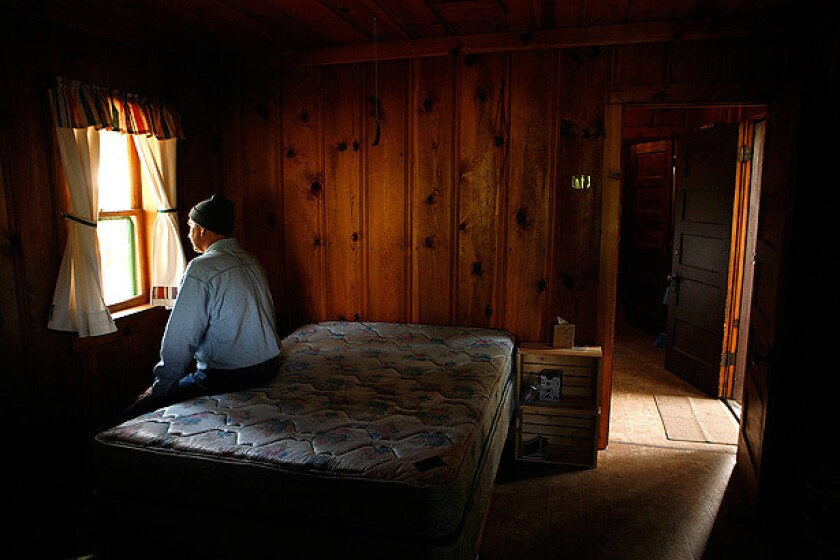 George Harper sits on the edge of his bed before taking down the curtains in his cottage.