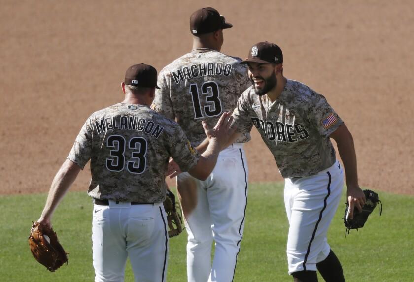 Padres teammates Mark Melancon and Eric Hosmer celebrate after victory.