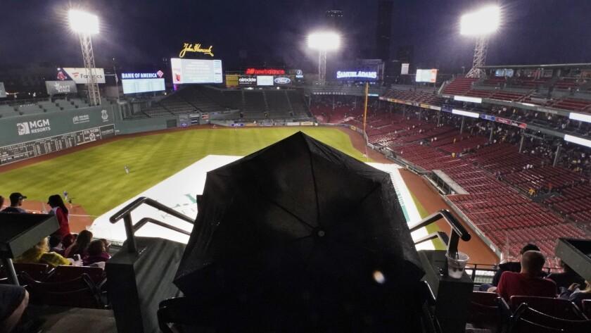 Un grupo de fanáticos espera a que pase la lluvia, que finalmente obligó a posponer el juego del martes 27 de julio de 2021, entre los Azulejos de Toronto y los Medias Rojas de Boston (AP Foto/Charles Krupa)
