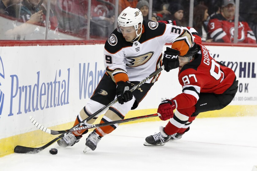 Anaheim Ducks center Sam Carrick (39) keeps the puck from New Jersey Devils left wing Nikita Gusev (97) during the second period on Wednesday in Newark, N.J.