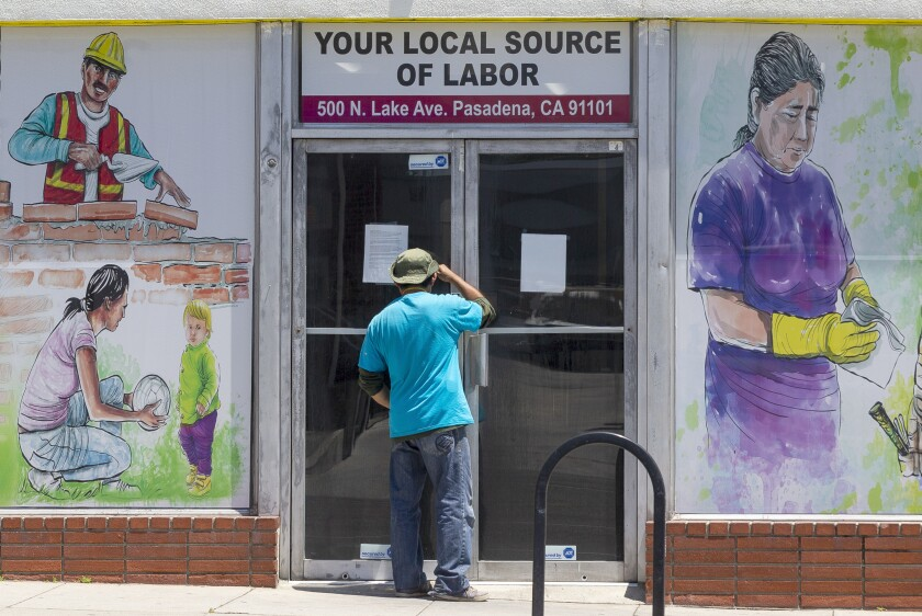 A worker looks inside the closed doors of the Pasadena Community Job Center on May 7