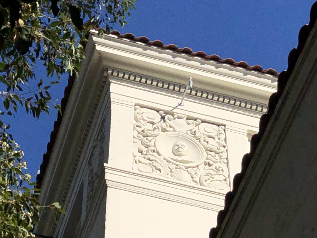 The corner of a building's ornate roofline, featuring a bas relief of a man and Spanish roof tile.