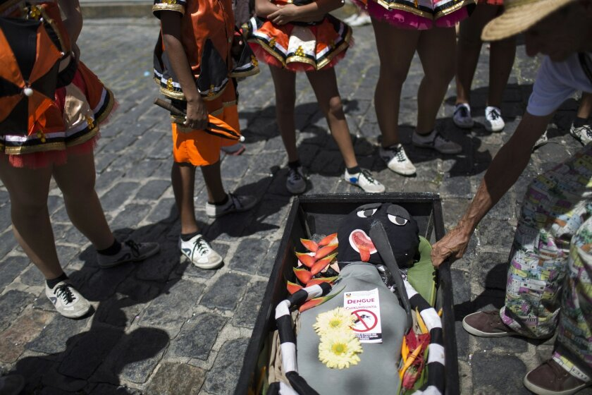 """A reveler drag a coffin containing an Aedes aegypti mosquito puppet during the """"Burial of the Mosquito"""" carnival block parade in Olinda, Pernambuco state, Brazil, Friday, Feb. 5, 2016. The parade that happens every year during carnival inform residents and tourists about the dangers of the Aedes ae"""