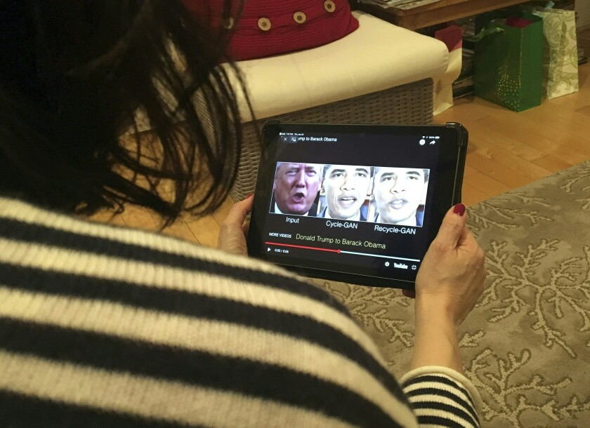 A woman views a manipulated video.