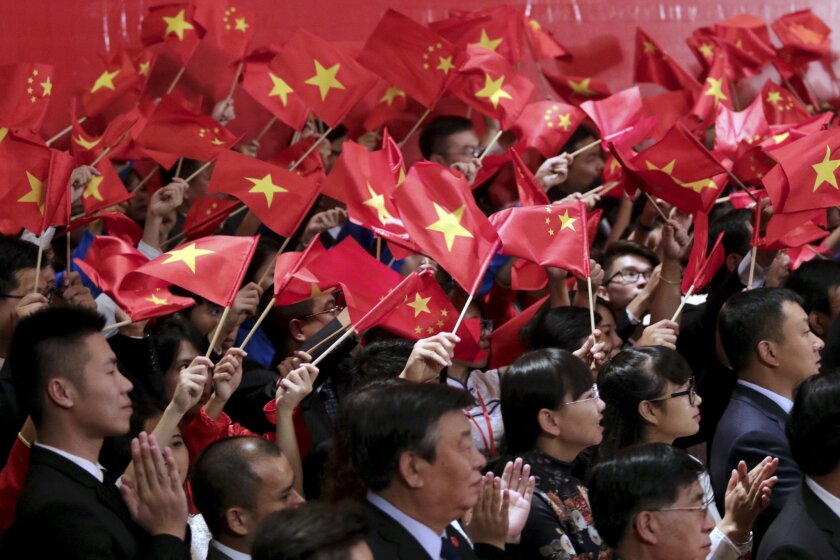 Vietnamese and Chinese communist youths wave flags to welcome Chinese President Xi Jinping and Vietnamese Communist Party General Secretary Nguyen Phu Trong at a meeting in Hanoi, Vietnam, Friday, Nov. 6, 2015. (AP Photo/Na Son Nguyen, Pool)