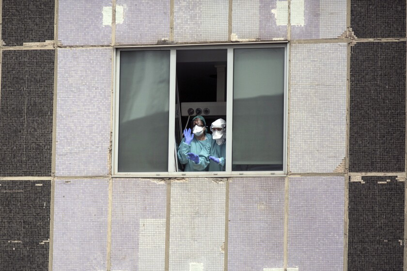 Medical workers wearing protective masks gesture from a hospital in Madrid on March 18.