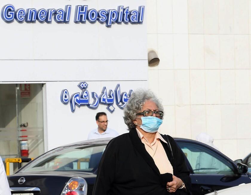 A woman wears a mask as she leaves a hospital Wednesday in the Red Sea coastal city of Jidda, Saudi Arabia.