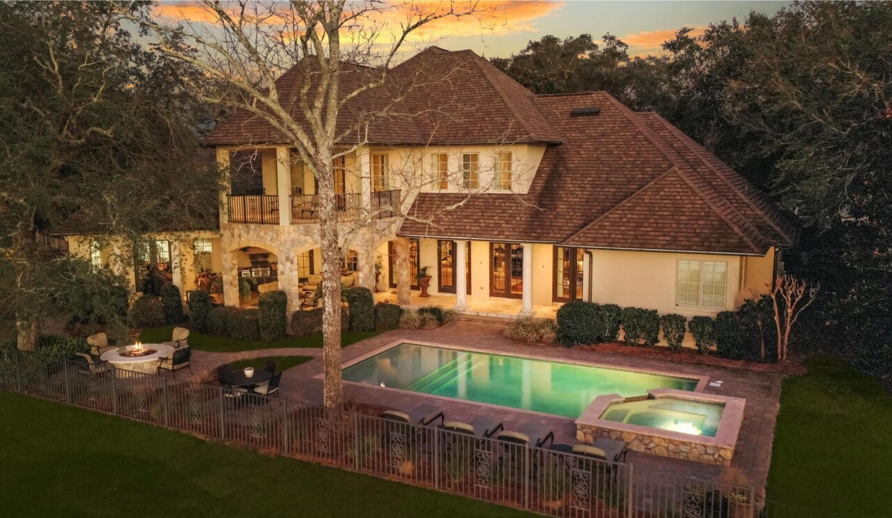 Built in 2011, the stone-clad home opens to an entertainer's backyard and a private dock on Rocky Bayou.