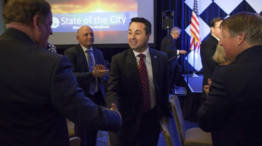 Newport Beach then-Mayor Kevin Muldoon, center, shakes hands with councilman Keith Curry in 2017
