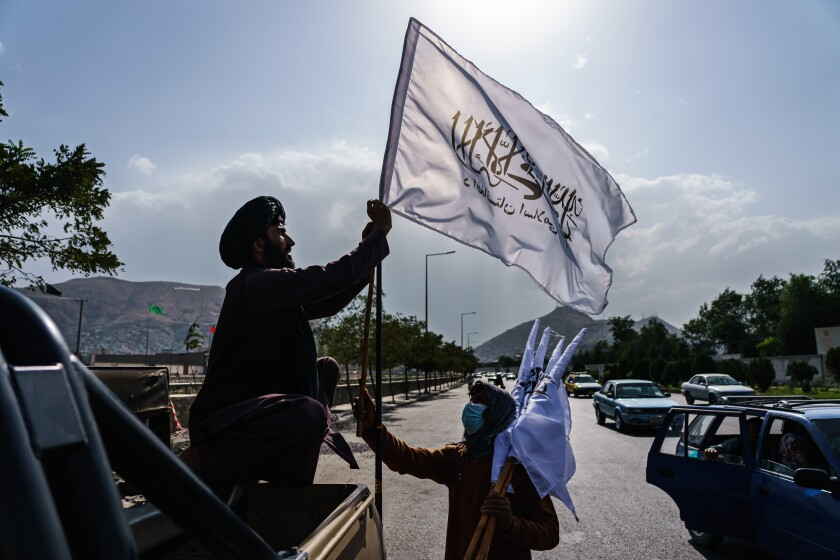 A boy with several white Taliban flags shows one to a man in a military vehicle