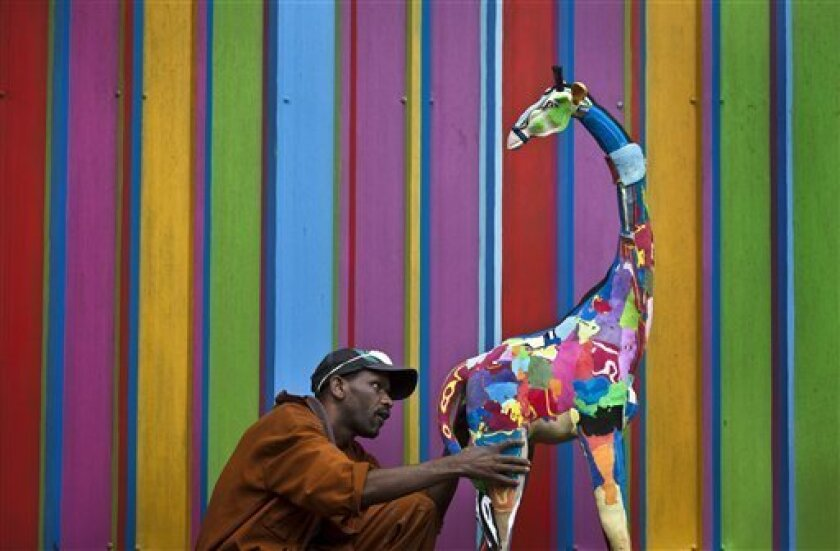 In this photo taken Monday, April 29, 2013, carver Jackson Mbatha, 40, poses next to an unfinished large toy giraffe he is making from pieces of discarded flip-flops, in front of a painted workshop wall at the Ocean Sole flip-flop recycling company in Nairobi, Kenya. The company is cleaning the East African country's beaches of used, washed-up flip-flops and the dirty pieces of rubber that were once cruising the Indian Ocean's currents are now being turned into colorful handmade giraffes, elepha