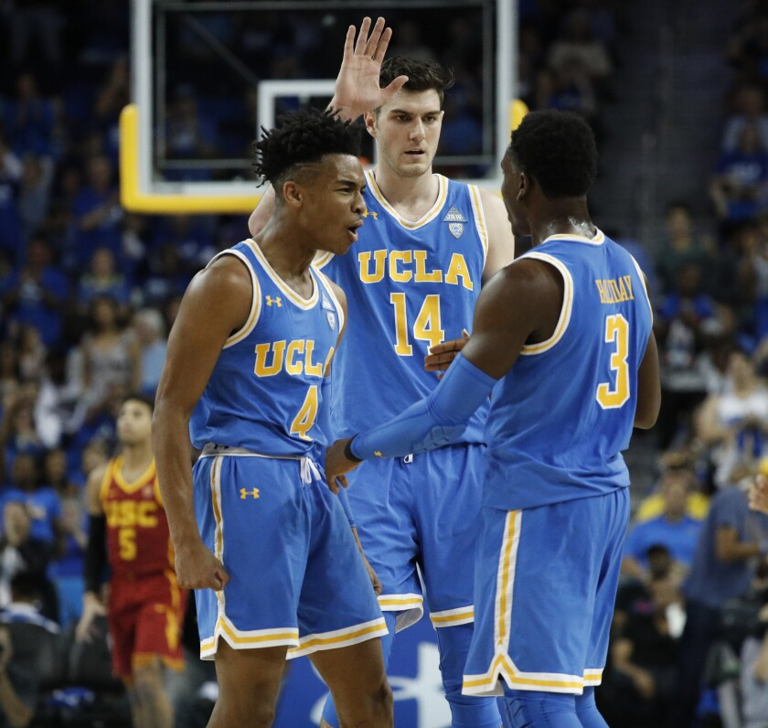 UCLA guard Aaron Holiday (3) is congratulated by guard Jaylen Hands (4) and forward Gyorgy Goloman (14) after sinking a three-point shot late in the game against USC at Pauley Pavilion on Feb. 3.