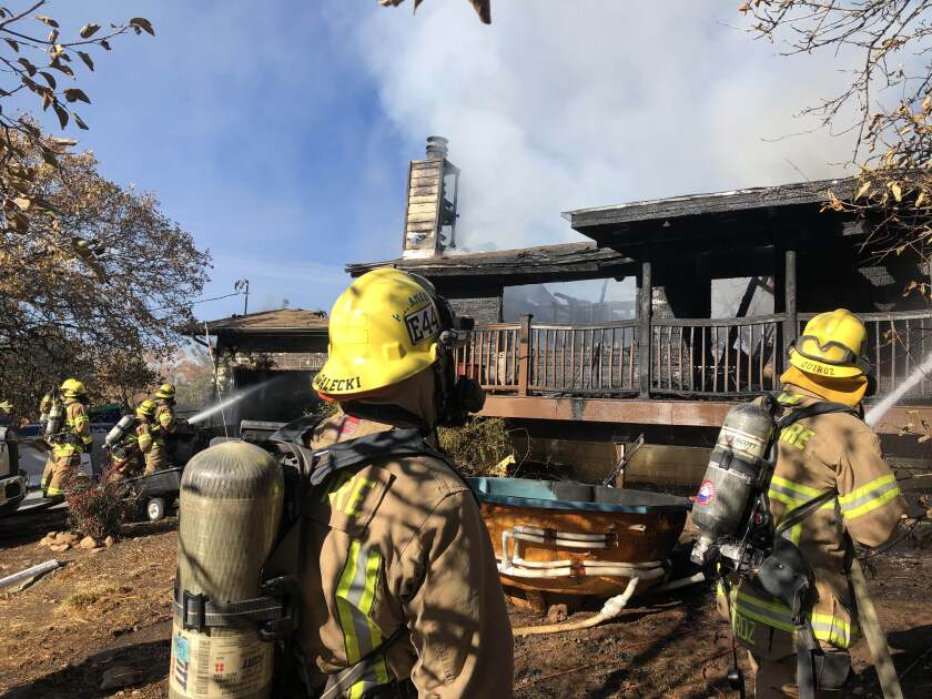 Cal Fire crews douse a fire that damaged a home in Julian on Sunday.