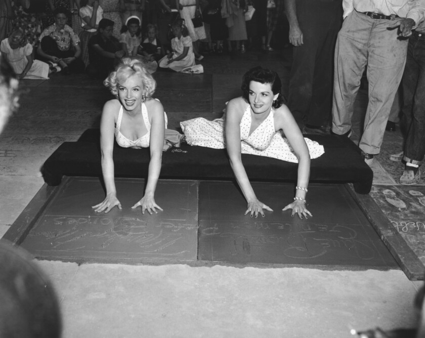 Marilyn Monroe, left, and Jane Russell leave their handprints at Grauman's Chinese Theater.