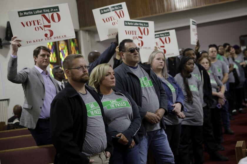 """In this Sunday, Nov. 3, 2019, photo, people wearing """"Save The Paseo"""" shirts stand among attendees at a rally to keep a street named in honor of Dr. Martin Luther King Jr. at Paseo Baptist Church in Kansas City, Mo. In January, the City Council voted to rename one of the city's main boulevards, The Paseo, after King, but many in the community want the old name back. A petition drive put the issue on the Nov. 5 ballot pitting neighbors against each other. (AP Photo/Charlie Riedel)"""