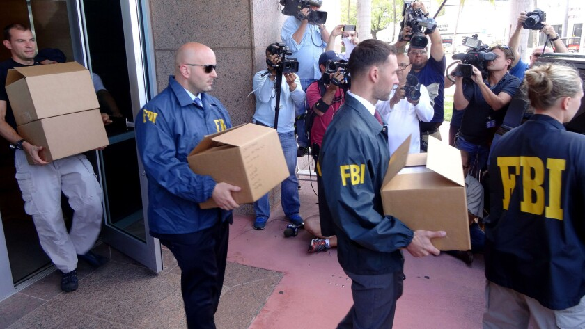 FBI agents take boxes with documents from the CONCACAF headqueartes in Miami Beach, Fla, on Wednesday.