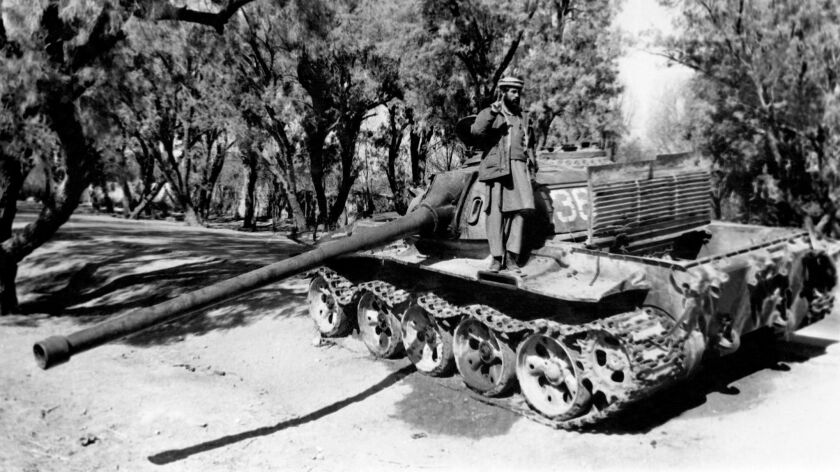 """An Afghan fighter stands on a captured Soviet tank in February 1989 east of Jalalabad, Afghanistan, days before the war ended. President Trump on Wednesday said of the 1979 Soviet invasion of the country: """"They were right to be there."""""""
