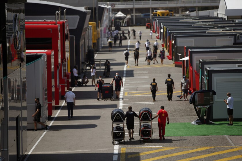 People walk through the paddocks before the Formula One Grand Prix at the Barcelona Catalunya racetrack in Montmelo, Spain, Thursday, Aug. 13, 2020. (AP Photo/Emilio Morenatti)