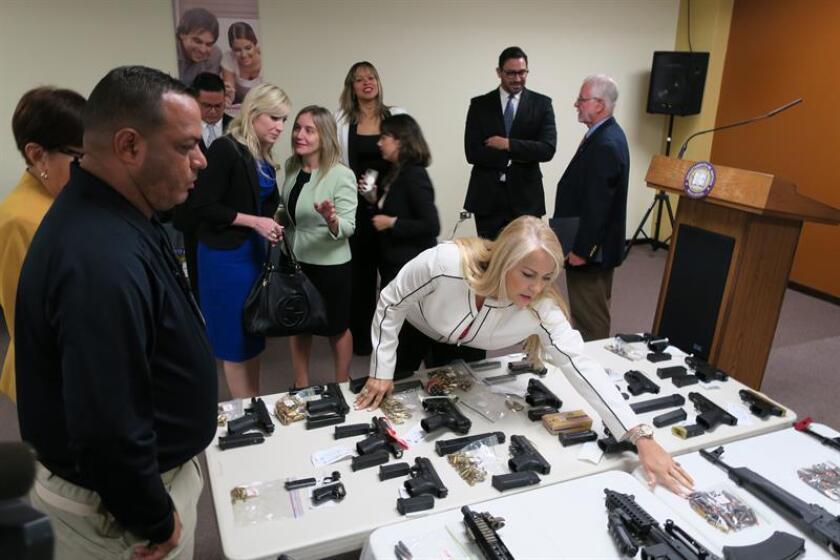 La secretaria de Justicia de Puerto Rico, Wanda Vázquez, verifica algunas de las 35 armas que las autoridades federales y locales incautaron a una decena de personas. EFE/Archivo