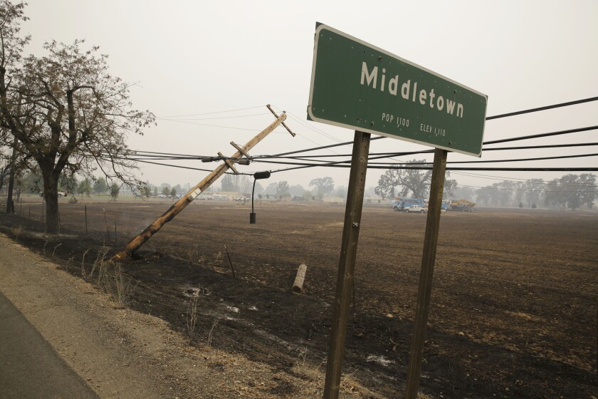 A downed power pole continues to burn along Highway 29 on Sunday in Middletown, Calif.