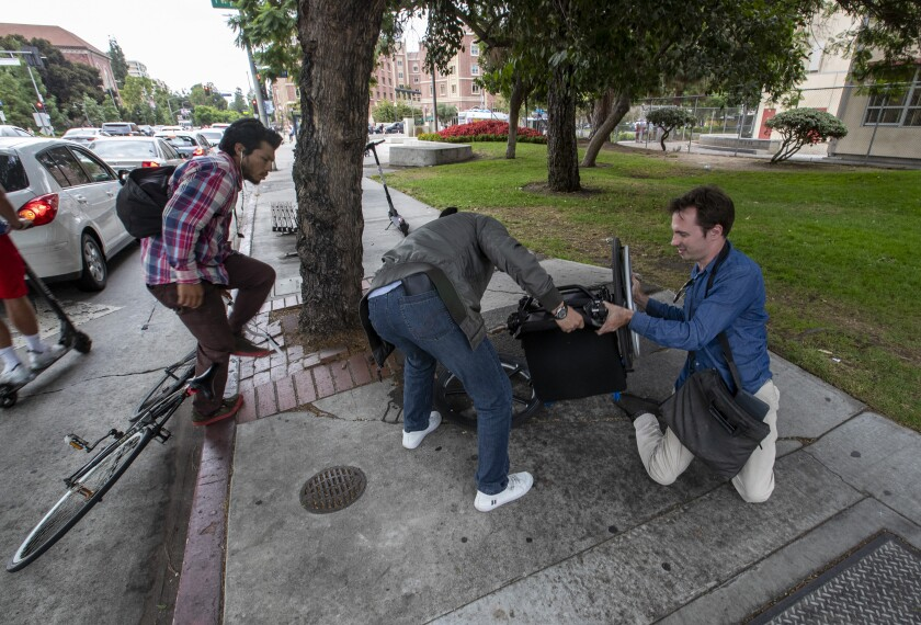 Passersby help David Radcliff back into his wheelchair.