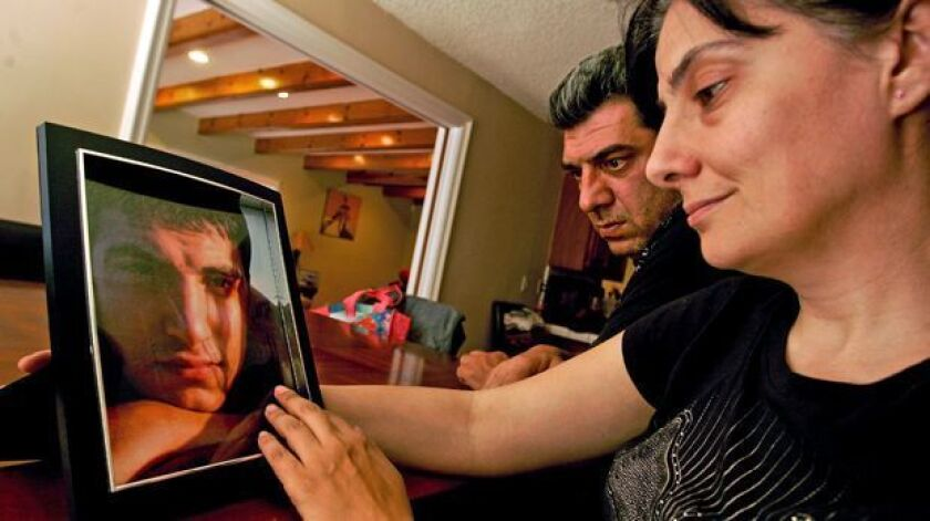 Artak Yepremyan and wife Ani Atajyan look at a photograph of their son Mike Yepremyan.