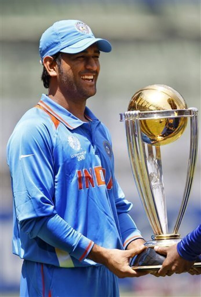India's captain Mahendra Singh Dhoni smiles as he poses with the Cricket World Cup trophy ahead of Saturday's final match between India and Sri Lanka in Mumbai, India, Friday, April 1, 2011. (AP Photo/Aijaz Rahi)