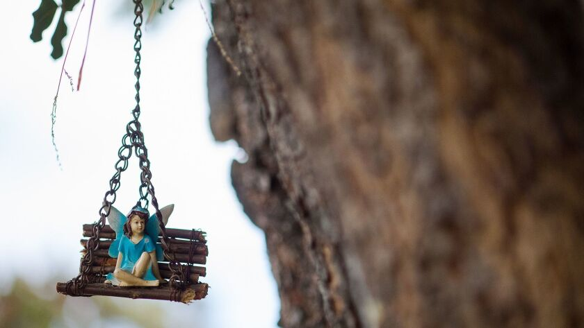 A fairy rests on a handmade swing.