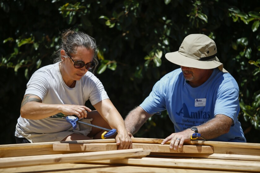 Denise Lozano and Rob Bird piece together a roof and wall support for the tiny house.